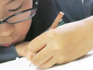 机に顔を近づけて勉強する子供
