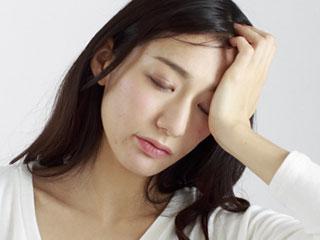 額を片手で押さえて目を閉じる女性