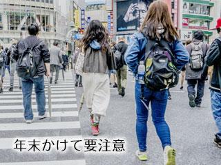 都会の交差点を歩く人々