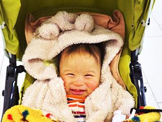 ベビーカーの中で笑う赤ちゃん