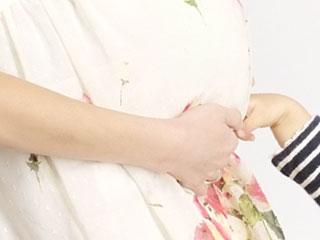 妊婦のお腹に触る子供の手