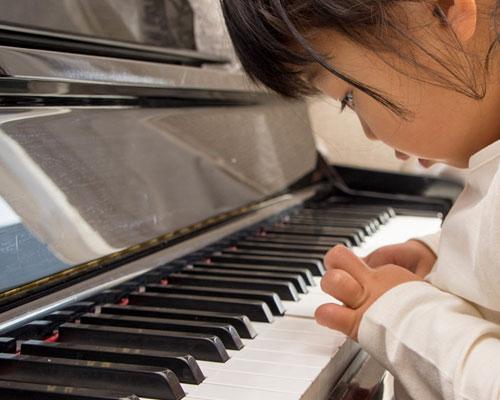 ピアノの鍵盤を指で押す女の子