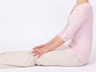 床に座って脚を伸ばす女性