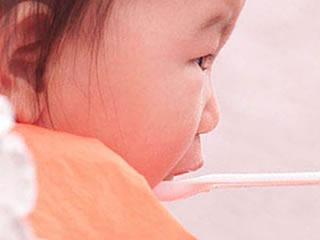 いやいや顔で離乳食を頬張る赤ちゃん