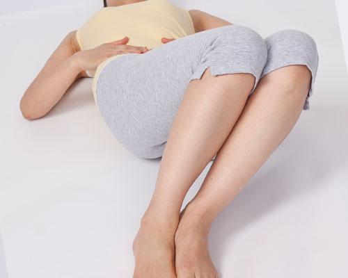 仰向けに寝て、立てた膝を曲げる女性