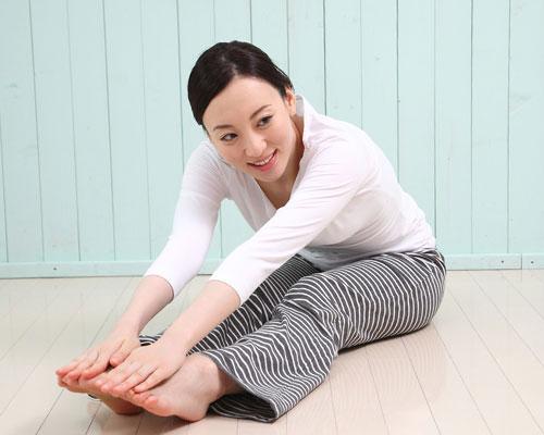 床で屈伸運動する女性