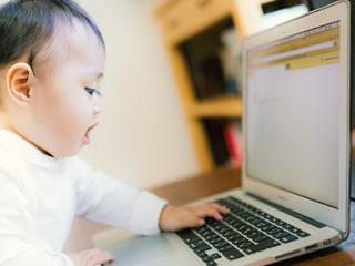 病名や診断方法をパソコンで調べる赤ちゃん