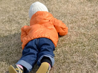芝生で匍匐前進する元気な子供