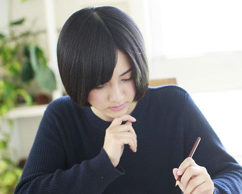 鉛筆で書き物する女性