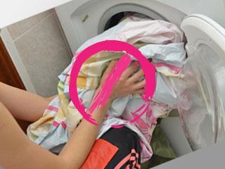 洗濯機へ洗物を入れる