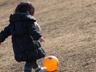 公園でサッカーボールを使って遊ぶ子供