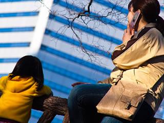 冬の公園で子どもと遊ぶ母親