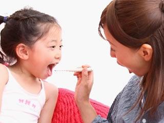 子供に歯磨きをするお母さん