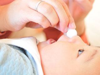 赤ちゃんの鼻に吸い取り器を当てる母親