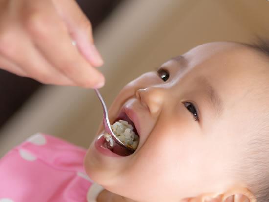 育児休業中の親にごはんを食べさせてもらう赤ちゃん