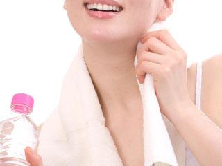 水ボトルを持ちながら汗を拭く女性