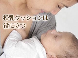 赤ちゃんを腕で抱える母親