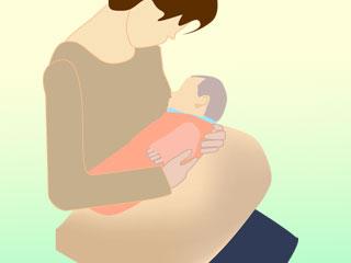 授乳クッションに赤ちゃんをのせて胸に抱く母親