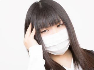 風邪をひいてマスクをする働く母親