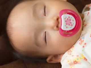 おしゃぶりをくわえスヤスヤ眠る女児