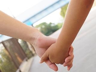 手を繋いで散歩する母親と子供