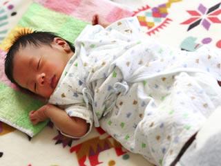 温かい毛布に包まれ眠る新生児