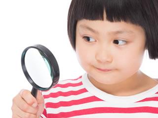 虫眼鏡で注目ポイントを照らす小学生