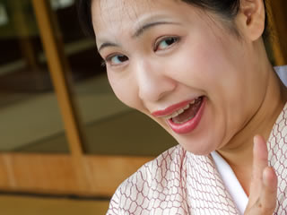 笑顔でピースサインをする旅館の女将