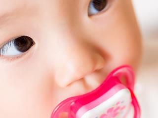 おしゃぶりをして遠くを見つめる赤ちゃん
