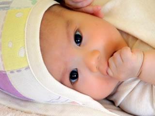 こちらを見つめおむつの交換を要求する赤ちゃん