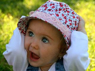帽子を両手で押さえる赤ちゃん