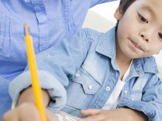 子供の宿題に付き合う父親