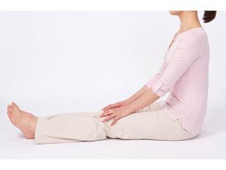 床に脚を伸ばして座る女性