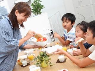 家庭で箸の持ち方を練習させる母親