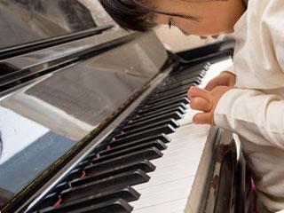 ピアノを指先で弾く女の子