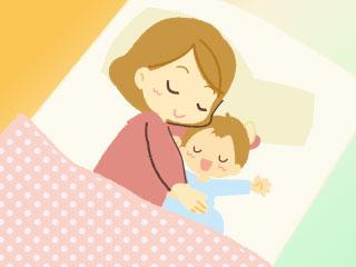 寝床で赤ちゃんを抱き寄せる母親