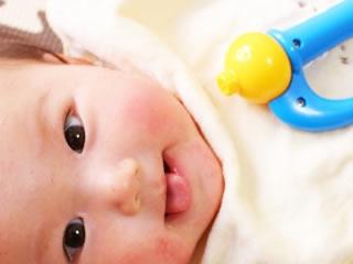 ツルツルお肌とおもちゃで機嫌が良い赤ちゃん