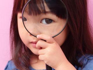虫眼鏡を覗く子供