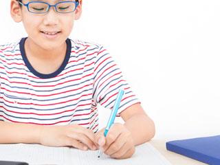 ノートに書く眼鏡を掛けた小学生