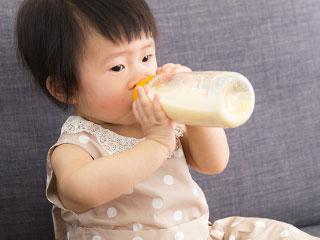 座って哺乳瓶を吸う赤ちゃん