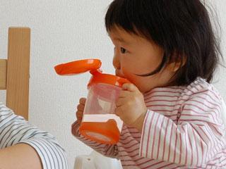 ストローマグでミルクを飲む赤ちゃん