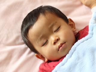 毛布の中で熟睡する男の子