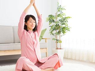 両手を挙げて座る妊婦