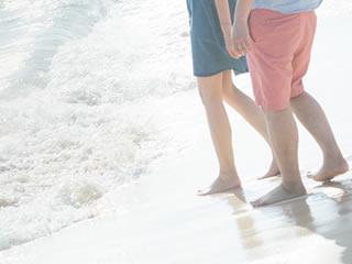 波打ち際を仲良く散歩する夫婦