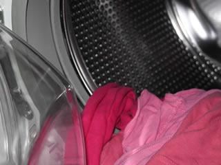 洗濯機に入れられる赤い毛布