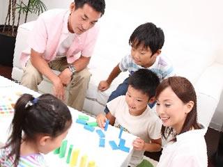 3人の子供とドミノで遊ぶ夫婦