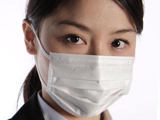 スーツ姿の女性がマスクをしている