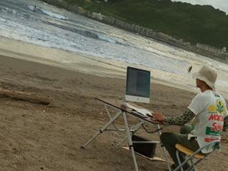 プライベートなので海岸でネットサーフィンを楽しむ男性