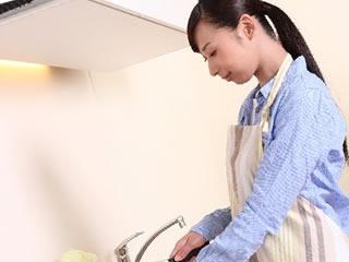 台所で子供のお弁当を作る母親