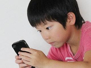 スマホのゲームに夢中になる小学生の男の子